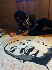 One of the event's young organizers, from Village Leadership Academy,  Kaleb Autman, works on a banner for the event.  Photo: Kelly Hayes